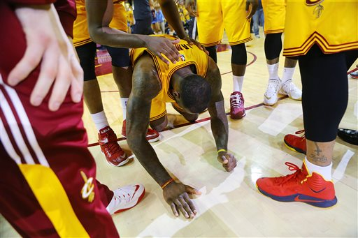 Cleveland Cavaliers' LeBron James falls to the floor as time expires in their game against the Atlanta Hawks in Game 3 of the Eastern Conference finals of the NBA basketball playoffs, Sunday, May 24, 2015, in Cleveland. The Cavaliers defeated the Hawks, 114-111, in overtime. (Curtis Compton/Atlanta Journal-Constitution via AP)