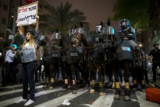 "An Israeli protester holds a sign in Hebrew reading ""violent policeman should be sentenced""  during clashes between Israel's, mainly Jewish Ethiopians and Israeli riot police during a protest against racism and police brutality in Tel Aviv, Israel, Sunday, May 3, 2015, as several thousand people from Israel's Jewish Ethiopian minority protest, shutting down a major highway and clashing with police on horseback long into the night. The protest was mostly peaceful during the day, but by nightfall became violent with at least 20 officers were hurt and ""multiple protesters"" arrested, Police Spokesman Micky Rosenfeld said. (AP Photo/Oded Balilty)"