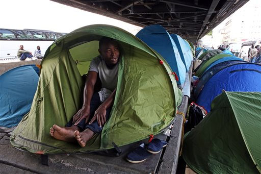 In this photo taken Monday, May 25, 2015, Mandela Drame, from Ivory Coast, speaks with The Associated Press as he sits in his tent placed alongside dozens of others set up by migrants under a metro bridge near the Gare du Nord station in Paris, France. Hundreds of migrants, mostly from east Africa, have poured into the ersatz tent camp on the bridge under a rumbling subway line and over tracks that take Eurostar trains to Britain. (AP Photo/Remy de la Mauviniere)