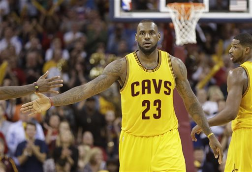 Cleveland Cavaliers forward LeBron James slaps hands with a teammate after scoring against the Chicago Bulls during the second half of Game 5 in a second-round NBA basketball playoff series Tuesday, May 12, 2015, in Cleveland. The Cavaliers won 106-101. (AP Photo/Tony Dejak)