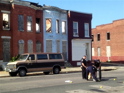 In this May 24, 2015, file photo, police pick up a pair of shoes after a double shooting in Baltimore. Residents in West Baltimore say they've been victims of excessive policing in this neighborhood where street crime and drug-dealing have been endemic. Now, one month after riots erupted in the wake of the death of Freddie Gray in police custody, homicides and shootings are up and those same residents feel like they've been abandoned and left to fend for themselves. (Colin Campbell/The Baltimore Sun via AP, File)