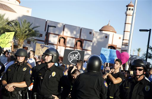 Protesters gather outside the Islamic Community Center of Phoenix, Friday, May 29, 2015. About 500 protesters gathered outside the Phoenix mosque on Friday as police kept two groups sparring about Islam far apart from each other.  (AP Photo/Rick Scuteri)