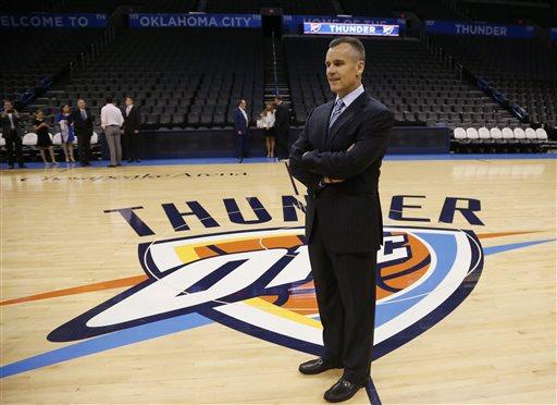 Billy Donovan, newly named head coach of the NBA Oklahoma City Thunder, poses for a photo on the Thunder logo prior to a news conference in Oklahoma City, Friday, May 1, 2015. (AP Photo/Sue Ogrocki)