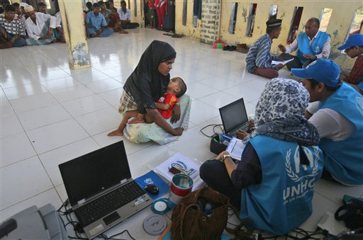 An ethnic Rohingya woman carries her baby as she answers questions from UNHCR workers at a temporary shelter in Lapang, Aceh province, Indonesia, Thursday, May 14, 2015. More than 1,600 migrants and refugees from Myanmar and Bangladesh have landed on the shores of Malaysia and Indonesia in the past week and thousands more are believed to have been abandoned at sea, floating on boats with little or no food after traffickers literally jumped ship fearing a crackdown. (AP Photo/Binsar Bakkara)