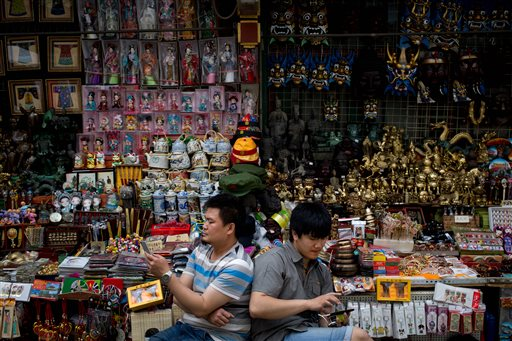 Vendors browse their smartphones as they wait for customer at their store selling Chinese made souvenirs at the Wangfujing shopping district in Beijing, China Thursday, May 21, 2015. Manufacturing in China shrank for the third straight month in May as demand remained soft, raising the chances of more stimulus to prop up growth in the world's No. 2 economy. (AP Photo/Andy Wong)