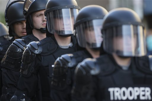 In this May 23, 2015, file photo, riot police stand in formation as a protest forms against the acquittal of Michael Brelo, a patrolman charged in the shooting deaths of two unarmed suspects in Cleveland. The city of Cleveland has reached a settlement with the U.S. Justice Department over a pattern of excessive force and civil rights violations by its police department, and the agreement could be announced as soon as Tuesday, May 26, 2015, a senior federal law enforcement official said. (AP Photo/John Minchillo, File)