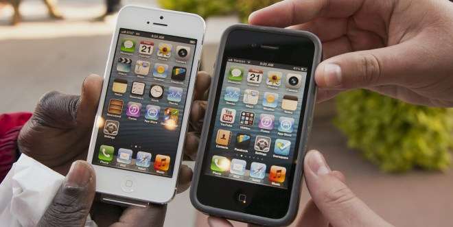 Noah Meloccaro, right, compares his older iPhone 4s to the new iPhone 5 held by Both Gatwech, outside the Apple Store in Omaha, Neb. (Nati Harnik/The Canadian Press/AP)