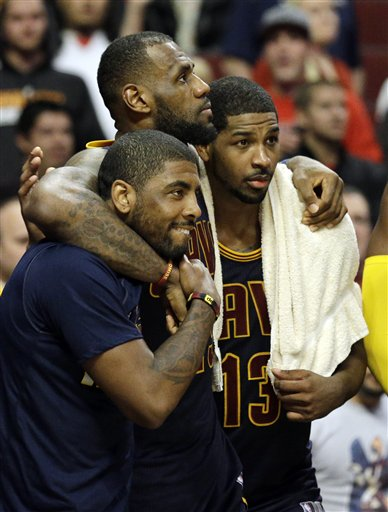 Cleveland Cavaliers forward LeBron James, center, watches the end of the game against the Chicago Bulls with guard Kyrie Irving, left, and center Tristan Thompson during the second half of Game 6 in a second-round NBA basketball playoff series in Chicago on Thursday, May 14, 2015. The Cavaliers won 94-73. (AP Photo/Nam Y. Huh)