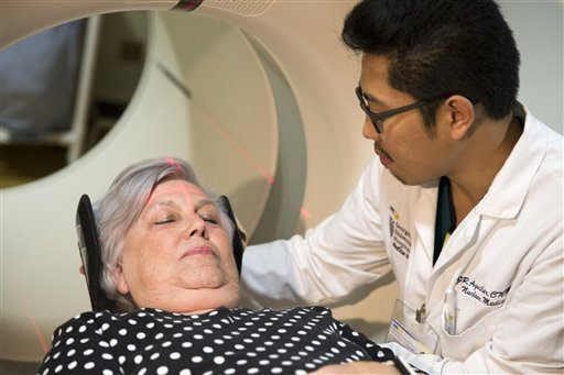 In this photo taken May 19, 2015, Judith Chase Gilbert, of Arlington, Va., is loaded into a PET scanner by Nuclear Medicine Technologist J.R. Aguilar at Georgetown University Hospital in Washington. Gilbert shows no signs of memory problems but volunteered for a new kind of scan as part of a study peeking into healthy brains to check for clues about Alzheimer's disease. (AP Photo/Evan Vucci)