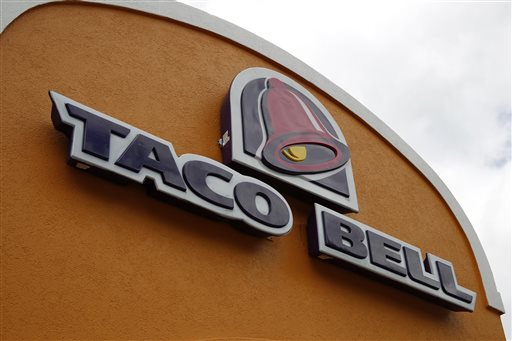 This Friday, May 23, 2014, file photo shows a sign at a Taco Bell in Mount Lebanon, Pa. Taco Bell and Pizza Hut say they're getting rid of artificial colors and flavors, making them the latest big food companies scrambling to distance themselves from ingredients people might find unappetizing. (AP Photo/Gene J. Puskar, File)