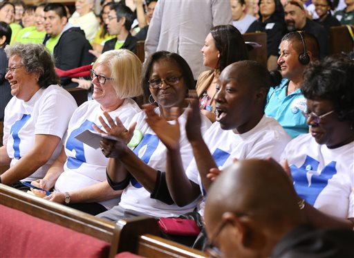 Supporters applaud during the minimum wage increase vote as the Los Angeles City Council votes to raise the minimum wage in the city to $15 an hour by 2020, making it the largest city in the nation to do so, in Los Angeles Tuesday, May 19, 2015. The measure approved Tuesday calls for small businesses with 25 or fewer employees to have an additional year to reach the $15 plateau. The council voted 14-1 after members of the public made impassioned statements for and against the plan. The increases begin with a wage of $10.50 in July 2016, followed by annual increases to $12, $13.25, $14.25 and then $15. Small businesses and nonprofits would be a year behind. (AP Photo/Damian Dovarganes)