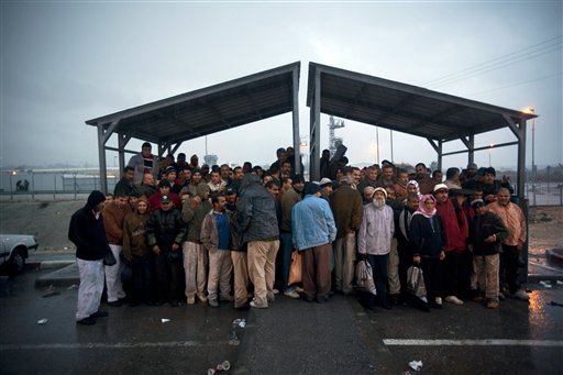 In this Nov. 3, 2009 file photo, Palestinian workers stand under a shelter to keep dry from the rain as they wait for transportation after crossing from the West Bank town of Qalqilya to work in Israel, at the Israeli army's checkpoint near Kibbutz Eyal in central Israel. Israeli Prime Minister Benjamin Netanyahu on Wednesday, May 20, 2015, called off a proposed plan to segregate Palestinians from Israelis on West Bank buses, overruling his defense minister amid a flurry of criticism in an attempt to avert the first crisis of his new government. (AP Photo/Oded Balilty, File)