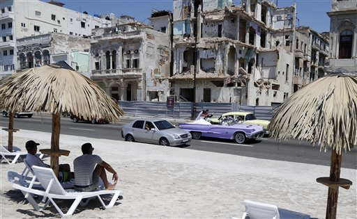 In this May 21, 2015, file photo, people sit on deck chairs on an artificial beach as a bride and groom ride a classic American convertible car on the Malecon in Havana, Cuba, Thursday. The beach's 40-year-old creator, Arles del Rio, sold a piece featured at the last biennial for $11,875, more than 40 times the annual salary of an ordinary Cuban. (AP Photo/Desmond Boylan, File)