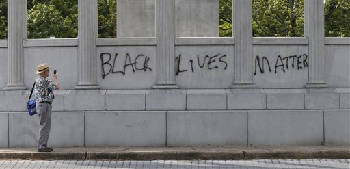 "A passerby photographs the spray painted message of ""Black Lives Matter"" that was painted on a monument to former Confederate President Jefferson Davis on Monument Avenue in Richmond, Va., Thursday, June 25, 2015. The vandalism comes after a mass shooting in Charleston South Carolina has sparked a nationwide debate on the public display of Confederate imagery.  (AP Photo/Steve Helber)"