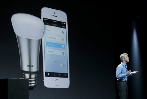 """In this June 2, 2014 file photo, Apple senior vice president of Software Engineering Craig Federighi speaks about the Apple HomeKit app at the Apple Worldwide Developers Conference in San Francisco. The first """"smart"""" home gadgets that can be controlled by Apple's voice-activated digital assistant are going on sale this week, just days after rival tech giant Google announced its own software for Internet-connected home appliances and other gadgets. (AP Photo/Jeff Chiu, File)"""