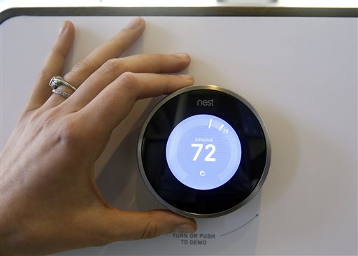 The Nest Learning Thermostat is on display following a news conference Wednesday, June 17, 2015, in San Francisco. Google's Nest Labs is releasing new versions of its surveillance video camera and talking smoke detector as part of its attempt to turn homes into yet another thing that can be controlled and tracked over the Internet. (AP Photo/Eric Risberg)