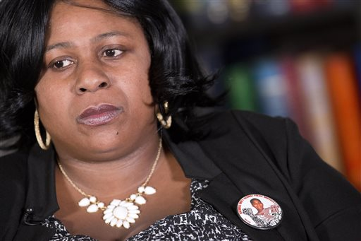 In this Dec. 15, 2014 file photo, Samaria Rice, of Cleveland, Ohio, wears a button with her son, Tamir Rice,  photograph during an interview at The Associated Press, Monday, Dec. 15, 2014 in New York.  Police say the investigation into the death of Rice, a 12-year-old boy fatally shot by a Cleveland policeman while he held a pellet gun has been turned over to county prosecutors. The Cuyahoga County sheriff's department said Wednesday, June 3, 2015,  its investigation into the shooting of Tamir Rice is complete. The county prosecutor has said the case will be presented to a grand jury that will determine if criminal charges are filed. (AP Photo/Mark Lennihan)