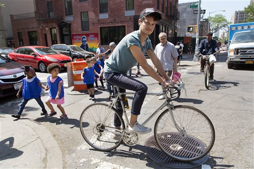 In this May 26, 2015 photo, freelance web designer Henry Brown cycles around his neighborhood in the Lower East Side of New York. Brown ditched his fledging advertising career 11 years ago, sick of spending 15 hours a day at work and having no time for himself. (AP Photo/Mark Lennihan)