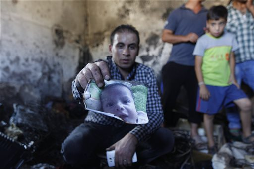 A relative holds up a photo of a one-and-a-half year old boy, Ali Dawabsheh, in a house that had been torched in a suspected attack by Jewish settlers in Duma village near the West Bank city of Nablus, Friday, July 31, 2015. The boy died in the fire, his four-year-old brother and parents were wounded, according to a Palestinian official from the Nablus area. (AP Photo/Majdi Mohammed)