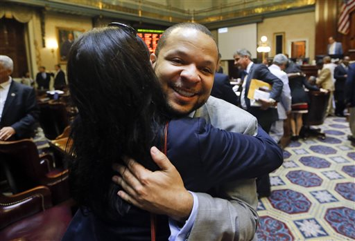 State Rep. John King, right, D-York, hugs a woman after the House approved a bill removing the Confederate flag from the Capitol grounds early Thursday, July 9, 2015, in Columbia, S.C. (AP Photo/John Bazemore)