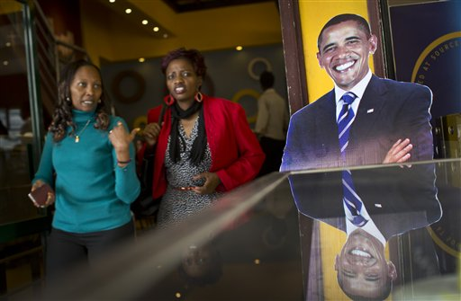 Customers walk past a cardboard cutout of President Barack Obama in the entrance way of the Cafe Deli coffee shop in Nairobi, Kenya, Wednesday, July 22, 2015.  In his first trip to Kenya since he was a U.S. senator in 2006, Obama is scheduled to arrive in Kenya on Friday, the first stop on his two-nation African tour in which he will also visit Ethiopia. (AP Photo/Ben Curtis)