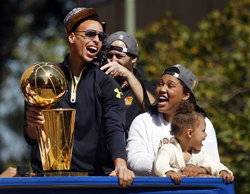 Golden State Warriors guard Stephen Curry, left, holds the Larry O'Brien Championship Trophy as he rides a bus with his daughter Riley, front right, and wife Ayesha as the procession turns onto Broadway in downtown Oakland, Calif., during a parade for the team's winning of the NBA basketball championship Friday, June 19, 2015. (Karl Mondon/San Jose Mercury News via AP)