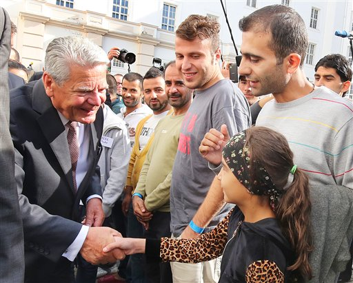 President Joachim Gauck visits a asylum-seeker home in  Berlin-Wilmersdorf and welcomes refugees in Berlin, Germany, Wednesday Aug. 26,  2015. German President Joachim Gauck and Chancellor Angela Merkel were visiting asylum seeker homes Wednesday to express support for refugees following an outburst of anti-foreigner violence over the weekend.  Merkel planned to meet with refugees, aid workers and local officials at a shelter in Heidenau, near Dresden, that had been at the center of neo-Nazi riots. (Wolfgang Kumm /dpa via AP)