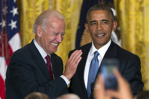 FILE - In this June 24, 2015 file photo Vice President Joe Biden and President Barack Obama speak in the East Room of the White House in Washington. President Barack Obama is the man in the middle as his vice president weighs challenging his former secretary of state for the 2016 Democratic nomination. While Obama would officially stay neutral in a Biden-Clinton face-off, the contest would essentially be a fight over which of his closest advisers is the rightful heir to his legacy. (AP Photo/Evan Vucci, File)