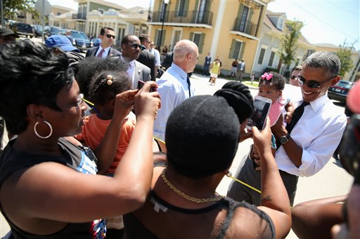 President Barack Obama, accompanied by New Orleans Mayor Mitch Landrieu, holds a child as he greets residents in the the Tremé neighborhood in New Orleans, Thursday, Aug. 27, 2015, for the 10th anniversary since the devastation of Hurricane Katrina.  Tremé is one of the oldest black neighborhoods in America, which borders the French Quarter just north of Downtown. (AP Photo/Andrew Harnik)