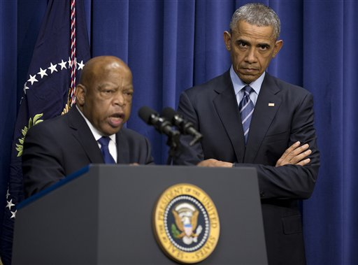 President Barack Obama listens as Rep. John Lewis, D-Ga. speaks in the South Court Auditorium in the Eisenhower Executive Office Building on the White House complex in Washington, Thursday, Aug. 6, 2015, on the 50th anniversary of the Voting Rights Act. (AP Photo/Carolyn Kaster)