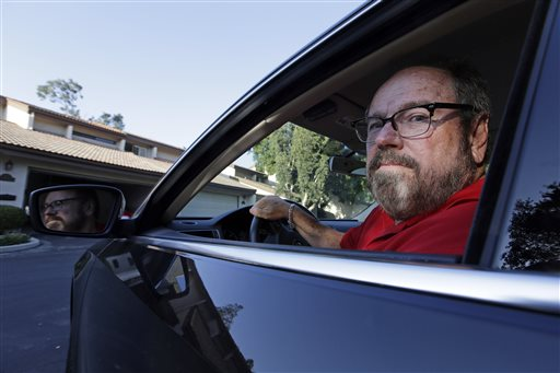 Bob Rand poses for a photo in his 2014, fully loaded Volkswagen diesel Passat on Wednesday, Sept. 23, 2015, in Pasadena, Calif. Rand convinced his son and his friend to buy the same car for environmental reasons. Now he's trying to sell it. (AP Photo/Chris Carlson)