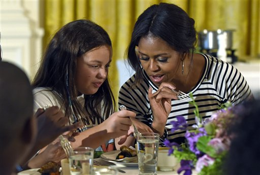 """In this Oct. 14, 2014 file photo, first lady Michelle Obama and a student look over their plates as they eat lunch in the East Room of the White House in Washington following the annual fall harvest of the White House Kitchen Garden. Congress will have to decide soon whether it wants another food fight with first lady Michelle Obama and the administration over what's served in the school lunch line. School food rules pitted Republicans seeking full exemptions for some schools against Obama in 2014, with the first lady declaring she'd fight """"to the bitter end"""" to make sure kids have good nutrition.(AP Photo/Susan Walsh, File)"""