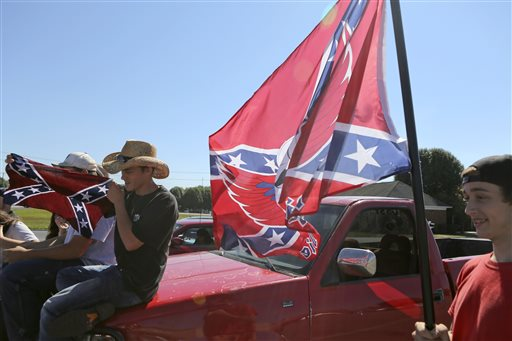 Christiansburg High School student Sam Sheppard, left, displays a Confederate flag while fellow student Andrew Love displays another flag in a shopping center parking lot after being suspended from school in Christiansburg, Va., Thursday, Sept. 17, 2015. Roughly 20 students at the Virginia high school received a one-day suspension for wearing clothing displaying the Confederate flag. A rally was also organized outside the school Thursday to protest a new school policy banning vehicles with Confederate symbols from its parking lot. (Matt Gentry /The Roanoke Times via AP)