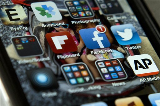 In this May 21, 2013 file photo, a view of an iPhone in Washington showing the Twitter app, right, among others. Think of it as tweeting for dollars. The social media service Twitter on Tuesday introduced a feature that enables political candidates and advocacy groups to raise money directly via its mobile application, making it quicker and easier to harvest small donations from followers. (AP Photo/Evan Vucci, File)