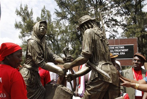 People gather near the sculpture of the Mau Mau war veterans at Uhuru park during  the unveiling of the Mau Mau veteran memorial in Nairobi, Kenya, Saturday, Sept. 12, 2015. (AP Photo/Khalil Senosi)