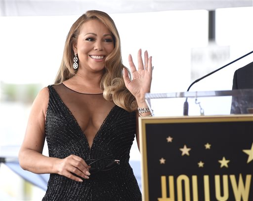 """In this Aug. 5, 2015 file photo, Mariah Carey attends a ceremony honoring her with a star on the Hollywood Walk of Fame in Los Angeles. A Cincinnati film commission has announced that pop singer Carey will be filming a Christmas movie in the region. WCPO-TV reports the Greater Cincinnati Film Commission said Tuesday, Sept. 15, 2015, the singer and actress is set to star in """"Melody & Mistletoe"""" in Cincinnati starting in October. (Photo by Chris Pizzello/Invision/AP, File)"""