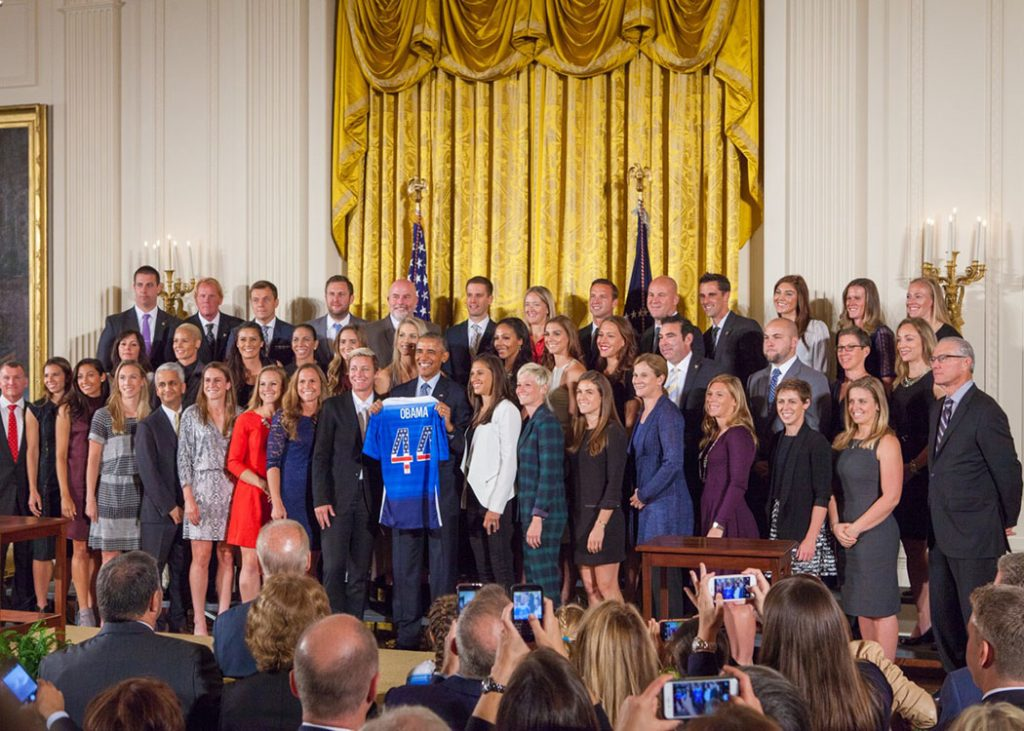 "President Obama welcomed the United States Women's National Soccer Team to the White House to honor the team and their victory in the 2015 FIFA Women's World Cup. The team presented Obama with a jersey with the number 44 on it. The FIFA trophy sits on a table next to the podium. ""These champions deserve all the attention they've been receiving,"" Obama said. (Cheriss May/HUNS)"