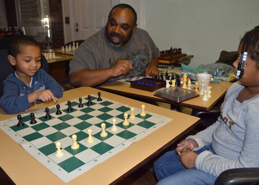 Ricky Norman, manager of the Big Chair Chess Club (center), shows two youngsters how to play chess during Chess Fun Day at the groups Deanwood location in Washington, D.C. (Ben Washington/AllEyesOnDC.com)