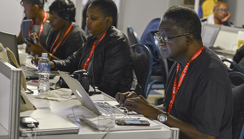Black Press icon George Curry works on a story in the media center at the 2016 International AIDS Conference in Durban, South Africa. (Freddie Allen/AMG/BAI)
