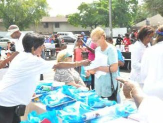 Community organizer Shirley Sharp hands out bags of books and school supplies at the Milwaukee Times table to attendees of the Northwest Funeral Home Back-to-School Book Bag Give-a-Way on Saturday, August 25, 2018