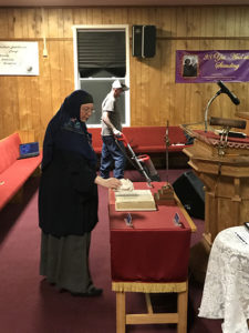 A woman looks at the vandalized Bible as a man cleans the carpet near a banner placed in the sanctuary to celebrate the 38 years served by the Rev. Richard Sibert at Walnut Grove Missionary Baptist Church. Photo courtesy of Rick Rodriguez, WGMBC Media Department