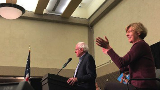 Bernie Sanders speaking at the rally with Tammy Baldwin by his side. (Photo by Nyesha Stone)