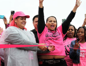With her sister Satra to her left, Compton City Councilwoman Janna Zurita cuts the ribbon, starting the seventh annual Compton Walk For A Cure at Centennial High School Oct. 13. A morning rainstorm may have resulted in fewer participants than normal. ()