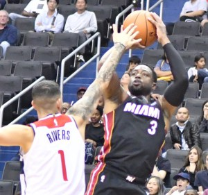 Miami Heat guard Dwyane Wade shoots over Washington Wizards guard Austin Rivers during the Wizards' 121-114 preseason win at Capital One Arena in D.C. on Oct. 5. (John De Freitas/The Washington Informer)
