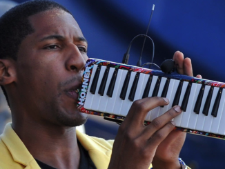 Jon Batiste performs on the melodica.