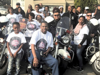 Pastor Harold Mayberry, the Senior Pastor at FAME (front) with Oakland police officers and members of the FAME community.