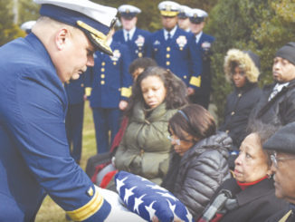 Rear Adm. Andrew Tiongson, commander First Coast Guard District, passes a folded American flag to a family member during funeral services for Dr. Olivia Hooker in White Plains, New York, Dec. 5, 2018. Dr. Hooker was the first African-American woman to enlist in the Coast Guard. Photo: Petty Officer 3rd Class Steve Strohmaier