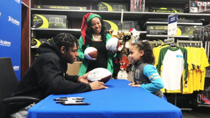 Shown is Jaguar Jalen Ramsey signing team footballs and wishing joy to Boys and Girls Club student Aketa Mills.