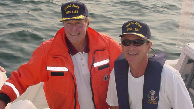 Former Presidents George H.W. Bush and George W. Bush don Coast Guard attire for the CGC ADAK after meeting the crew during security operations near the Bush family residence in Kennebunkport, N.J.