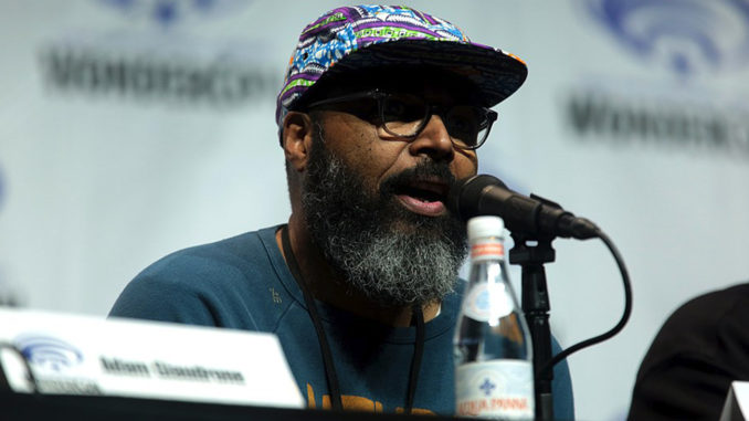 """Salim Akil speaking at the 2018 WonderCon, for """"Black Lightning"""", at the Anaheim Convention Center in Anaheim, California"""